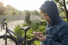 Young Teenager Man With Smartphone And Bike stock images
