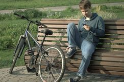 Young Teenager Man With Smartphone And Bike.  royalty free stock images