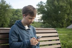 Young Teenager Man With Smartphone in City Park royalty free stock images
