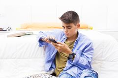 Young teenager with the mobile phone. In the room Royalty Free Stock Images