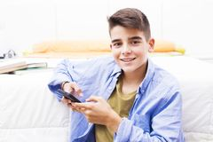 Young teenager with the mobile phone. In the room Stock Images