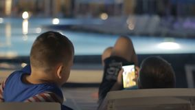 Young teenager playing game on smartphone near pool. Young teenager playing game on smartphone. Children are entertained in the pool area online. Kids have stock video footage