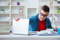 The young teenager preparing for exams studying at a desk indoors stock photography