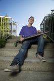 Young teenager sitting while holding his longboard Stock Photography