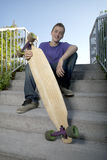 Young teenager sitting while holding his longboard Royalty Free Stock Photography