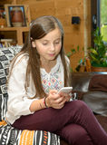 Young teenager on the sofa sends a text message. Young teenager girl on the sofa sends a text message Royalty Free Stock Images