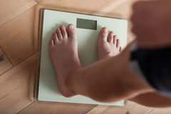 Young teenager weighing himself on a scale Stock Photo