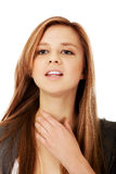 Young teenager woman touching her neck.  Stock Photo