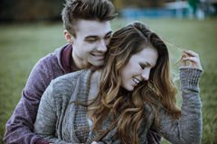Young teenagers flirting outdoors. Playful young couple sitting on the grass and hugging, they are laughing and enjoying Stock Photography