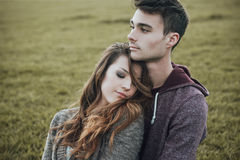 Young teenagers flirting outdoors. Young teenagers outdoors, sitting on the grass and cuddling, he is hugging his girlfriend, relationships and feelings concept Royalty Free Stock Photography