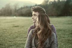 Young teenagers flirting outdoors. Young teenagers outdoors, sitting on the grass and cuddling, he is hugging his girlfriend, relationships and feelings concept Stock Photography
