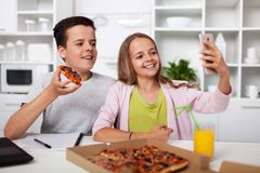 Young teenagers taking a selfie with each other and the pizza they share in the kitchen stock photography