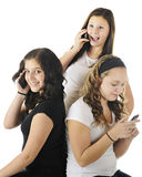 Young Teens Phoning. Three young teens using technology to communicate with other friends.  On a white background Stock Photo