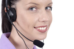 Young adult female telephonist with telephone headset, smiling, eyes looking at camera, close up Royalty Free Stock Photos