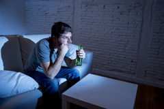 Young television addict man sitting on home sofa watching TV and drinking beer bottle Royalty Free Stock Images