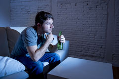 Young television addict man sitting on home sofa watching TV and drinking beer bottle. Looking mesmerized enjoying movie sitcom or live sport at night Royalty Free Stock Images