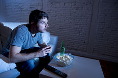 Young television addict man sitting on home sofa watching TV eating popcorn and drinking beer bottle. Looking mesmerized enjoying movie sitcom or live sport at royalty free stock photography