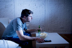 Young television addict man sitting on home sofa watching TV eating popcorn and drinking beer bottle. Looking mesmerized enjoying movie sitcom or live sport at Stock Photos