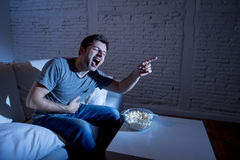 Young television addict man sitting on home sofa watching TV and eating popcorn laughing crazy Stock Photo