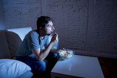 Young television addict man sitting on home sofa watching TV and eating popcorn Royalty Free Stock Images