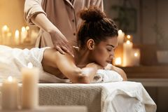 Tender african girl smiling enjoying massage with closed eyes in spa resort. Young tender african girl smiling enjoying massage with closed eyes in spa resort Royalty Free Stock Image