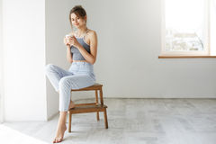 Young tender brunette girl smiling holding cup looking at camera sitting on chair over white wall early in morning. Copy space Stock Photography