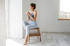 Young tender brunette girl smiling holding cup looking at window enjoying view sitting on chair over white wall in. Morning. Copy space Royalty Free Stock Images
