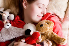 Young tender girl sleeping with her toys.  Stock Photos