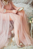 A young, tender pregnant is holding a vintage mirror in her hands. Royalty Free Stock Images