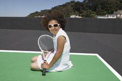 Young tennis girl. Mixed race girl rests on court with a tennis racket Stock Images