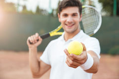 Young tennis man giving ball stock images