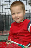Young tennis player. Adorable little boy sitting next to the tennis net with a racket in his hands, smiling Stock Photography