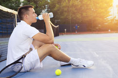 Young tennis player drinking water after practice. Young tennis player drinking water after playing, sitting on court and looking at sunset Stock Image