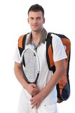 Young tennis player with equipments smiling. Young tennis player going to training, holding backpack and tennis racket, smiling Stock Images