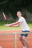 Young tennis player hitting ball. On a sunny day Royalty Free Stock Photography