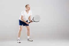 Young tennis player plays tennis on grey background stock photography