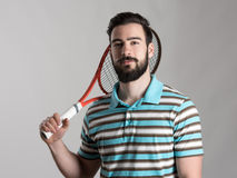 Young tennis player in polo shirt holding racket Stock Photo