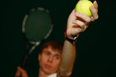 The young tennis player with a racket. The young sportsman in the sports form beats a tennis racket on a tennis ball Royalty Free Stock Photography