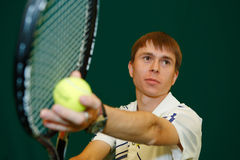 The young tennis player with a racket. The young sportsman in the sports form beats a tennis racket on a tennis ball Stock Photo