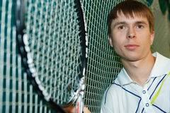 The young tennis player with a racket. The young sportsman in the sports form beats a tennis racket on a tennis ball Royalty Free Stock Image