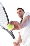 Young tennis player serving. Young male tennis player preparing for serve, concentrating Stock Image