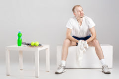 Young tennis player with towel resting after workout. Young tennis player with towel resting after a workout Stock Photography