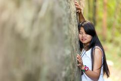 Young Thai girl holding onto a rock Stock Images