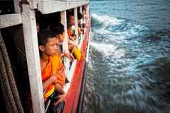 Young Thai monk takes a taxi boat Royalty Free Stock Photos