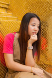 Young Thai women distracted. And rest her chin on hand with golden tile texture in background Stock Photo