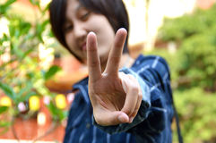 Young thai women shows sign victory. Young thai woman shows sign victory background garden Stock Photography