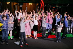 Young theatergoers. children enthusiastically watching children's Christmas puppet show theatre Smeshariki. Stock Photography