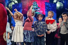 Young theatergoers. children enthusiastically watching children's Christmas puppet show theatre Smeshariki. Royalty Free Stock Images