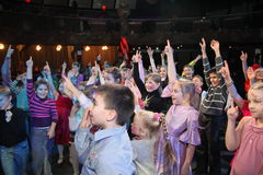 Young theatergoers. children enthusiastically watching children's Christmas puppet show theatre Smeshariki. Stock Photos