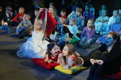 Young theatergoers. children enthusiastically watching children's Christmas puppet show theatre Smeshariki. Royalty Free Stock Photos